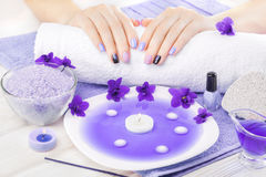 Beautiful purple manicure with violet, candle and towel on the white wooden table. Royalty Free Stock Photography