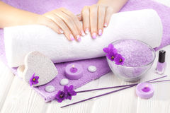 Beautiful purple manicure with violet, candle and towel on the white wooden table. Stock Images