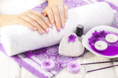 Beautiful purple manicure with violet, candle and towel on the white wooden table. Royalty Free Stock Photo
