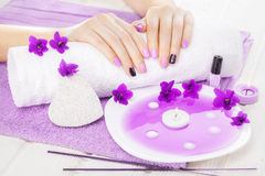 Beautiful purple manicure with violet, candle and towel on the white wooden table. Stock Image