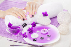 Beautiful purple manicure with violet, candle and towel on the white wooden table. Royalty Free Stock Image