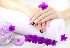 Beautiful purple manicure with violet, candle and towel on the white wooden table. Stock Photos