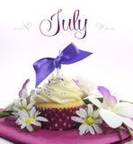 Beautiful purple and pink Summer theme cupcake with seasonal flowers and decorations for the month of July Stock Photos