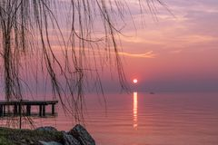 Beautiful purple sunset during fog on Lake Garda with a silhouette of a fishermen boat in the background. Italy royalty free stock photography