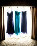 Beautiful purple and teal bridesmaid dresses hanging in a window Stock Photography