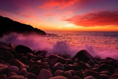 Purple tinted waves breaking on a rocky beach at sunset over Porth Nanven in the Cot Valley of Cornwall, England Royalty Free Stock Image