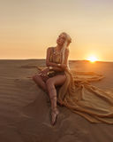 Beautiful queen of the desert in a luxurious gold dress. Stock Photos