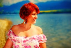 Beautiful radiant girl with red hair and colorful sommer dress beside a lake. Beautiful radiant girl with red hair and colorful sommer dress beside a lake stock photos