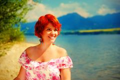 Beautiful radiant girl with red hair and colorful sommer dress beside a lake. Beautiful radiant girl with red hair and colorful sommer dress beside a lake Royalty Free Stock Photography