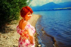 Beautiful radiant girl with red hair and colorful sommer dress beside a lake. Beautiful radiant girl with red hair and colorful sommer dress beside a lake Stock Image