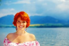 Beautiful radiant girl with red hair and colorful sommer dress beside a lake. Beautiful radiant girl with red hair and colorful sommer dress beside a lake Stock Photo