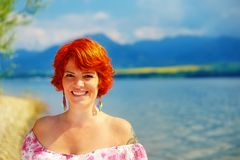 Beautiful radiant girl with red hair and colorful sommer dress beside a lake. Beautiful radiant girl with red hair and colorful sommer dress beside a lake Royalty Free Stock Photo
