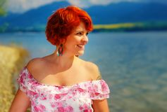 Beautiful radiant girl with red hair and colorful sommer dress beside a lake. Beautiful radiant girl with red hair and colorful sommer dress beside a lake Stock Images