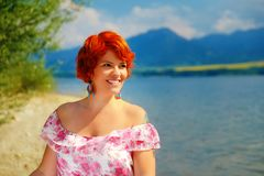 Beautiful radiant girl with red hair and colorful sommer dress beside a lake. Beautiful radiant girl with red hair and colorful sommer dress beside a lake Royalty Free Stock Photos