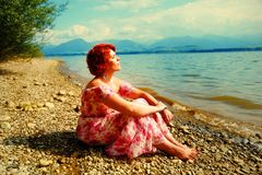 Beautiful radiant girl with red hair and colorful sommer dress beside a lake. Beautiful radiant girl with red hair and colorful sommer dress beside a lake royalty free stock image