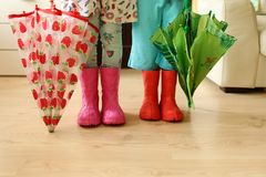 Children in rainboots colourful wear pretty cool and umbrellas royalty free stock photos