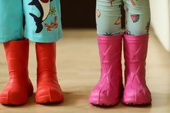 Children in rainboots colourful wear pretty cool and umbrellas Royalty Free Stock Image
