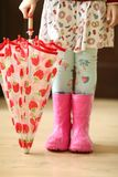 Children in rainboots colourful wear pretty cool and umbrellas Stock Photo