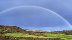 Beautiful rainbow in the blue sky over a golf course. A wonderful colorful rainbow in the blue sky over a green golf course on the Spanish Atlantic island of Royalty Free Stock Photography