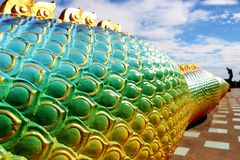 Beautiful Rainbow colors of Praya Nark or Naga in Thai temple with colorful sky and sun flare effect on sunrise time Royalty Free Stock Images