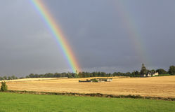 Beautiful rainbow in dark sky over field the Stock Image