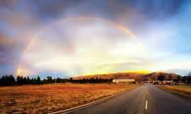 Rainbow formed after rain in the middle of the road. A beautiful rainbow formed after rain in New Zealand. This photo was taken in the middle of the road. New stock image