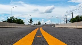 Middle lane of the road before the end of curve on the bridge and beautiful blue sky background in the countryside of Thailand. Beautiful rainy sky background Royalty Free Stock Images