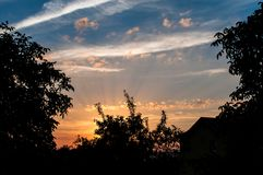 Beautiful rays of the sun during sunset in the countryside, birds flying in the sky royalty free stock photography