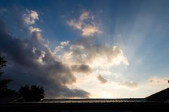 Sunbeams shine over rain clouds during sunrise in rural Illinois stock images