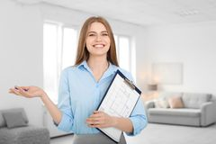 Beautiful real estate agent with clipboard. Indoors stock photography