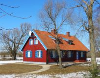 Beautiful rebuild home in village, Lithuania. Nice red wooden home in village Minge in winter, Lithuania royalty free stock photography
