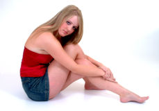 Beautiful In Red. Female sitting on floor, wearing red bodice & blue skirt Stock Photo