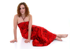 Beautiful In Red. Female wearing red dress sitting on floor Royalty Free Stock Photography