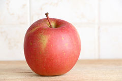 A beautiful red apple on a chopping board Stock Photography