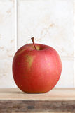 A beautiful red apple on a chopping board Royalty Free Stock Photo