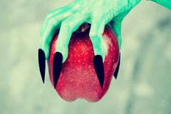 Beautiful red apple in green hands of old witch with black nails. Fairytale scary. mystical and fantasy scene with green hands and red apple royalty free stock images