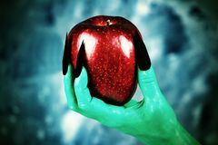 Beautiful red apple in green hands of old witch with black nails. Fairytale scary. mystical and fantasy scene with green hands and red apple royalty free stock image