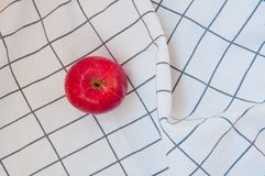 Beautiful red apple on the white folded towel royalty free stock image
