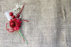 A beautiful red artificial flower with a green stem on the texture of a brown old linen cloth, linen natural material with a rough. Perpendicular interlacing of Royalty Free Stock Photo