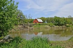 Beautiful red barn on the eroding banks of a river Stock Image