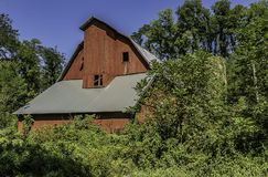 Beautiful red barn in a rural area. An aging red barn in a rural area. A true vintage American barn stock photo
