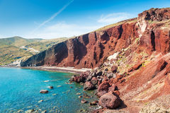 Beautiful Red Beach with turquoise water and big rocks Stock Image