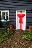 Beautiful red bow tied on a exterior door, a Christmas decoration. Essex, England, UK - December 15, 2017: Beautiful red bow tied on an exterior door. A stock photos
