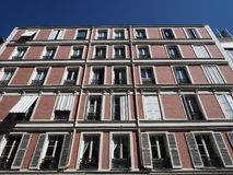 Beautiful red brick building soars into blue sky. Building façade made of red bricks soars into blue sky in Paris, France royalty free stock photography