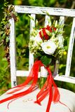 Beautiful red bridal bouquet is standing on a chair in the park.  Stock Images