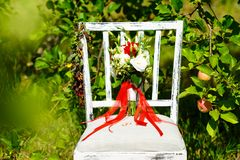 Beautiful red bridal bouquet is standing on a chair in the park.  Stock Image