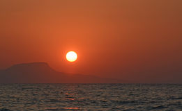Beautiful Red Bright Sunset on the sea. Island Crete. Amazing Red Orange Sunset. Cool summer background Stock Photo