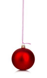 Beautiful red Christmas ball hanging with pink ribbon on a white background. Royalty Free Stock Photo