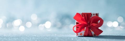 Beautiful red christmas gift with large bow on shiny blue background and defocused christmas lights in the background. Christmas banner with copy space royalty free stock images