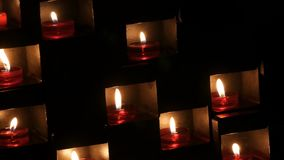 Beautiful red church candles for prayers in special niches in a catholic temple on black background stock video footage